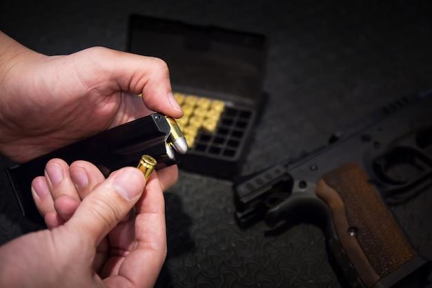 El artillero recarga su cargador de pistola, arma de arma, bala del bloque de balas en el campo de tiro para la práctica de tiro