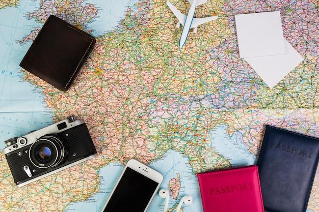 Artilugios electrónicos con pasaporte y billetera en el mapa mundial