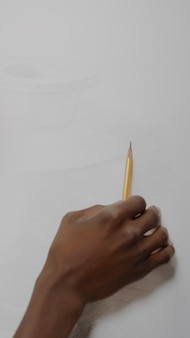 Artista afroamericano creando dibujo de jarrón con lápiz