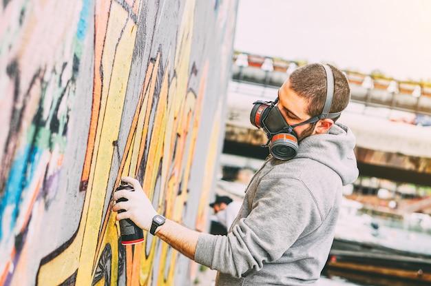 Artista callejero pintando coloridos graffiti en una pared debajo del puente