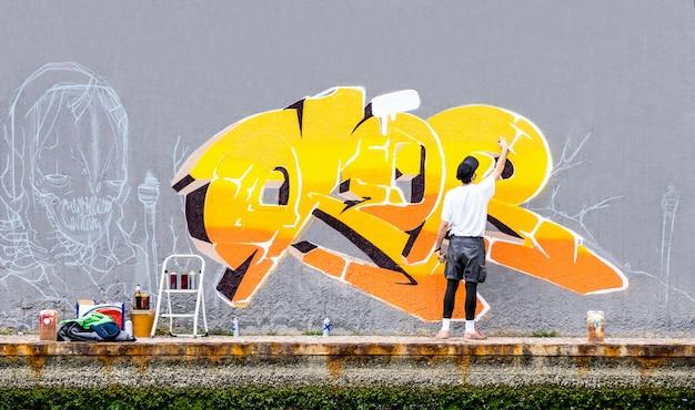 Artista callejero pintando graffiti de colores en la pared del espacio público