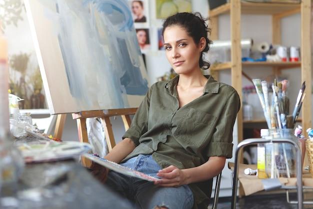 Una artista caucásica joven con talento y de aspecto positivo que se relaja en una silla junto al caballete en el taller después de que ella terminó su pintura. profesión, arte creativo, moderno, trabajo y ocupación.