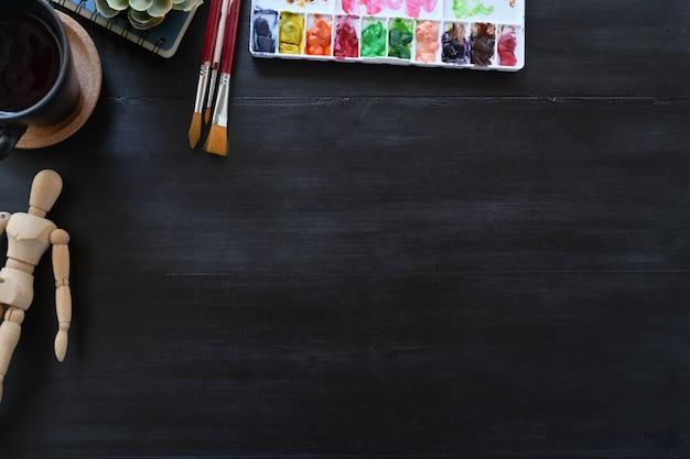 Artista de color del espacio de trabajo con accesorios creativos en mesa de madera oscura. espacio de trabajo y espacio de copia.