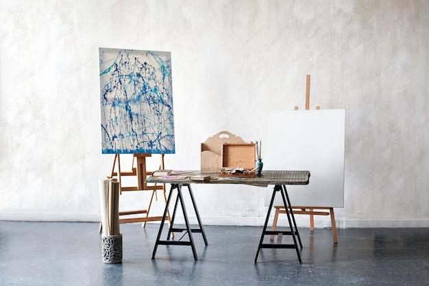 Artista creativo lugar de trabajo sin aficiones de personas. estudio de pintura de un artista independiente. caballete, lienzo, pinceles, lápices, pinturas con álbumes sobre la mesa. el interior en el estudio del artista, taller.
