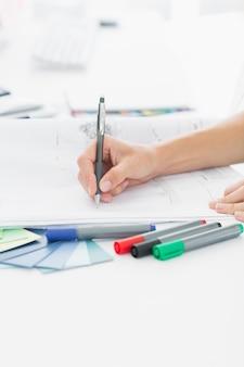 Artista dibujando algo en papel con lápiz en la oficina