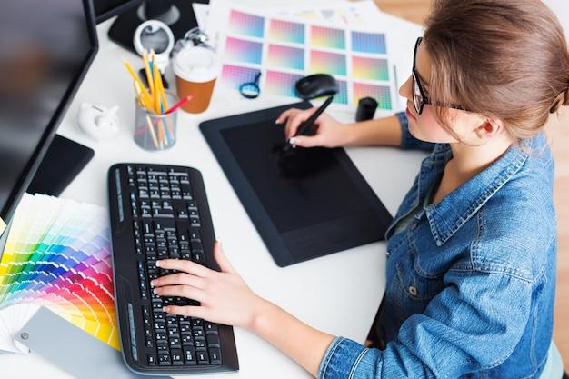 Artista dibujando algo en tableta gráfica en la oficina