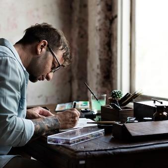 Artista dibujando en su mesa.
