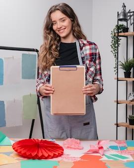 Artista femenina atractiva feliz mostrando portapapeles con papel marrón liso