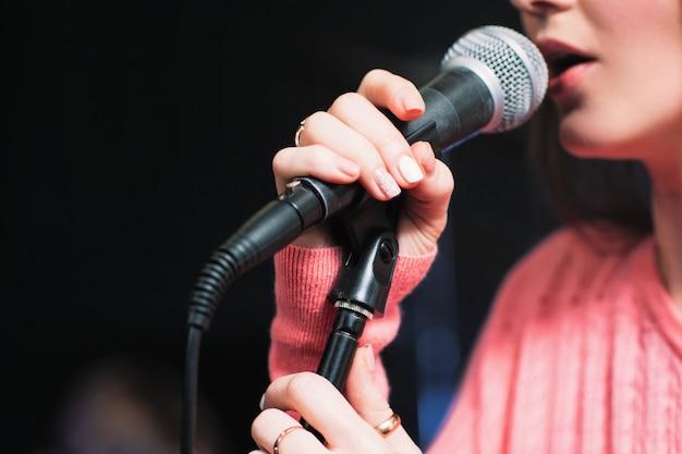 Artista femenina cantando en un micrófono