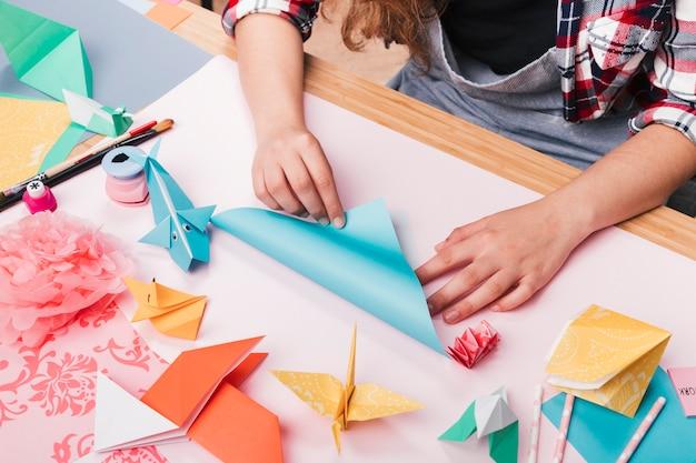 Artista femenina doblando papel de origami para hacer bellas artesanías.