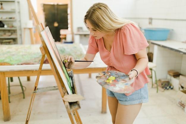 Artista femenina haciendo pintura sobre caballete con pincel