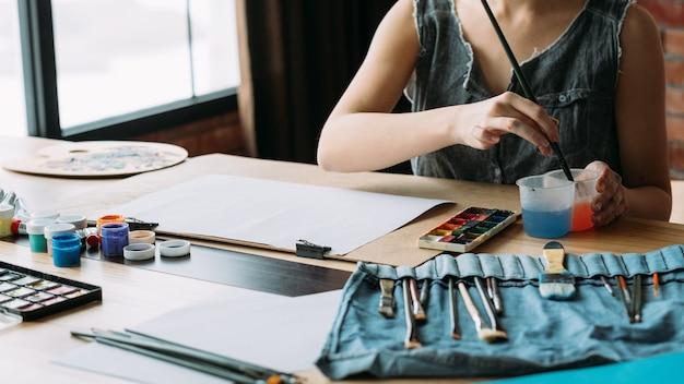 Artista femenina pintando en el espacio de trabajo creativo