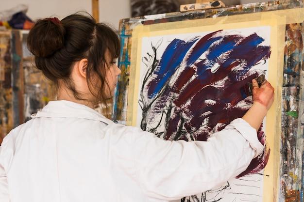 Artista femenina profesional pintando sobre lienzo con pincel.