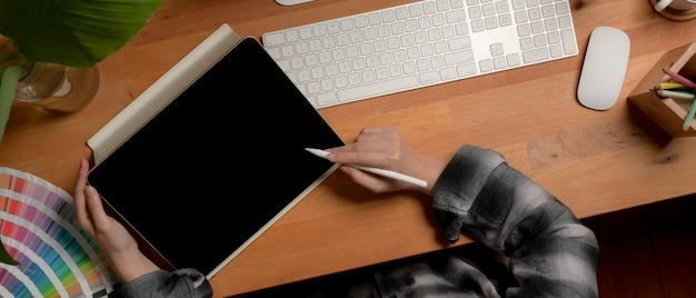 Artista femenina trabajando en escritorio de oficina de madera con tableta digital, computadora, suministros y decoraciones