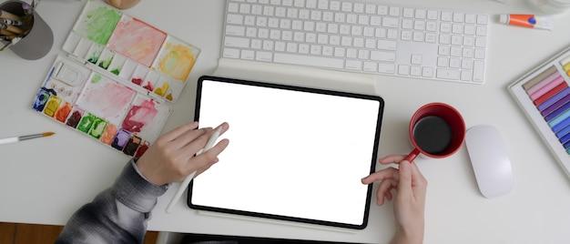 Artista femenina trabajando con tableta de pantalla en blanco, herramientas de pintura y tomando café en el escritorio de oficina