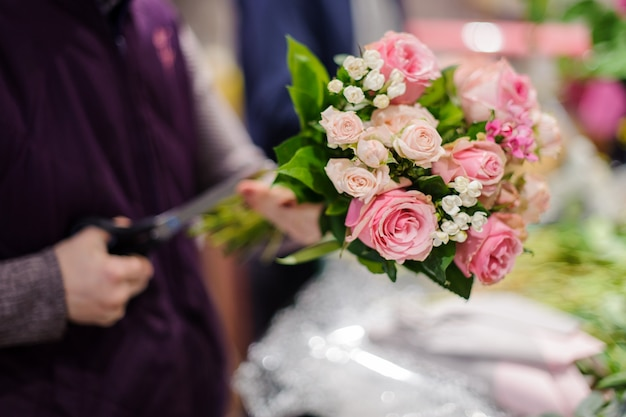 Artista floral haciendo un hermoso ramo de rosas rosadas