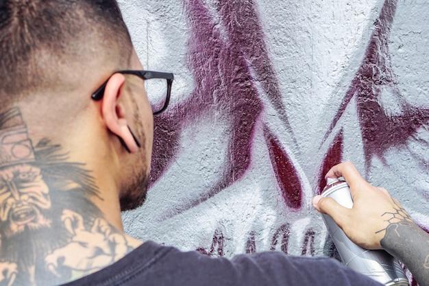 Artista de graffiti callejero que pinta con una lata de aerosol de color un cráneo de monstruo oscuro graffiti