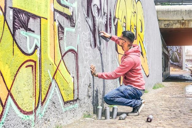 Artista de graffiti callejero que pinta con una lata de aerosol de color un graffiti de cráneo de monstruo oscuro en la pared de la ciudad al aire libre - concepto de arte urbano contemporáneo de estilo de vida urbano - foco principal en su mano