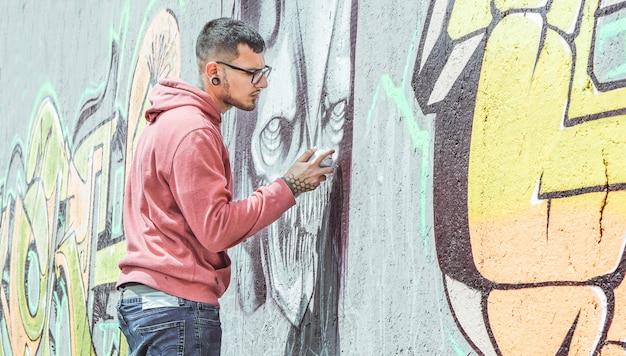 Artista de graffiti callejero que pinta con una lata de aerosol de color un graffiti de cráneo de monstruo oscuro en la pared de la ciudad - concepto de arte urbano, estilo de vida urbano - foco principal en su mano