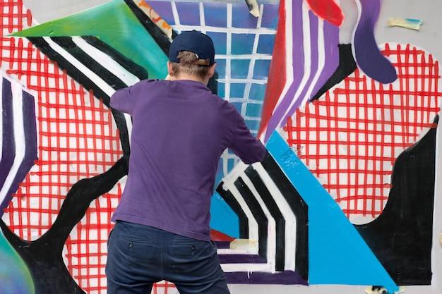 Artista de graffiti pintando coloridos graffiti en la pared