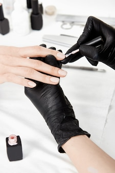 Artista de uñas en guantes aplicando capa base en el dedo anular.