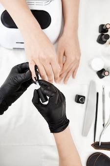Artista de uñas en guantes aplicando capa base en el dedo meñique.