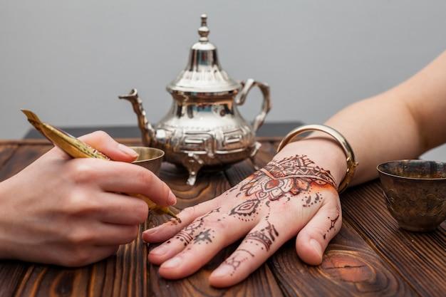 Artista haciendo mehndi en mano de mujer cerca de tetera