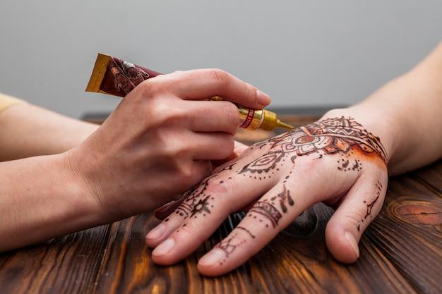 Artista haciendo mehndi en mano de mujer en mesa