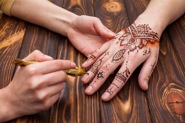 Artista haciendo mehndi en mano de mujer