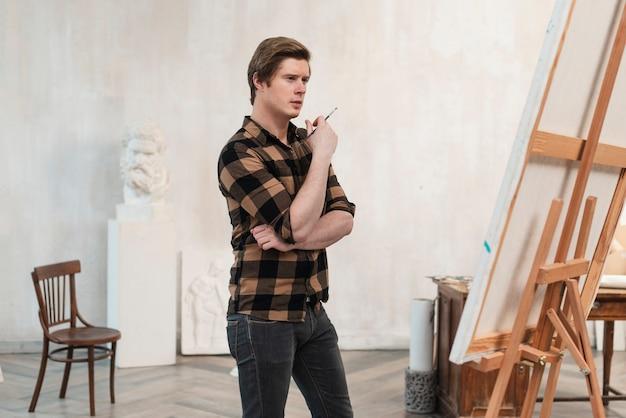 Artista de hombre de lado mirando su pintura