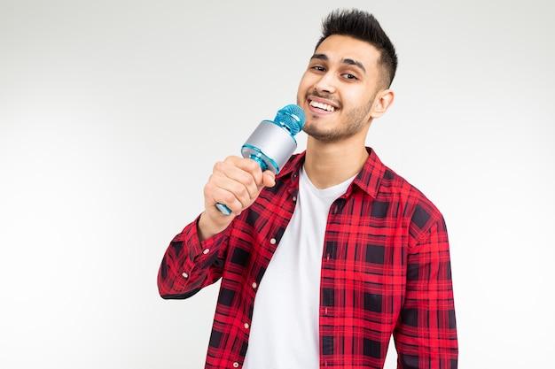 Artista intérprete o ejecutante cantante en una camisa con un micrófono en sus manos sobre un blanco