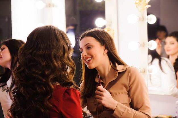 Artista de maquillaje aplica lápiz labial. rostro de mujer hermosa. maquillaje perfecto