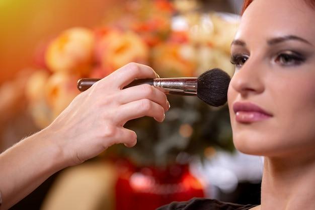 Artista de maquillaje aplicando base tonal líquida en el rostro de la mujer en la sala de maquillaje blanco.
