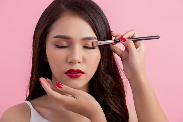 Artista de maquillaje aplicando delineador líquido con pincel.