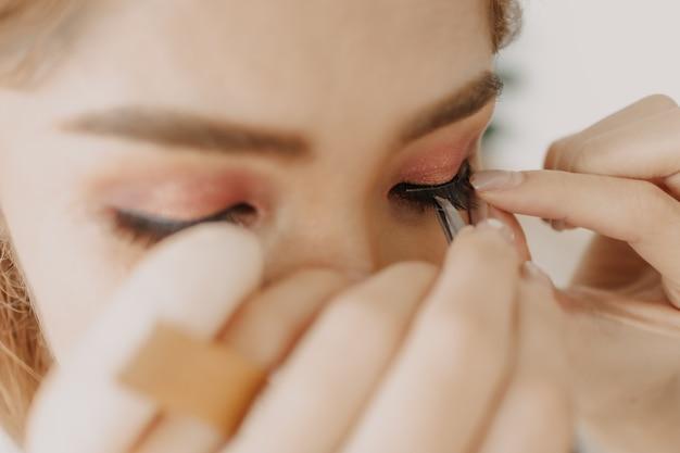 Artista de maquillaje está aplicando maquillaje en los ojos del cliente