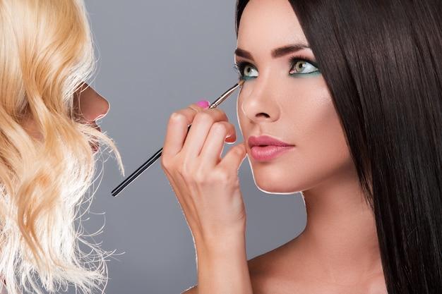 Artista de maquillaje aplicando sombra de ojos en ojos modelo
