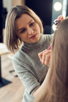 Artista de maquillaje aplicar delineador de ojos en el modelo de cultivo