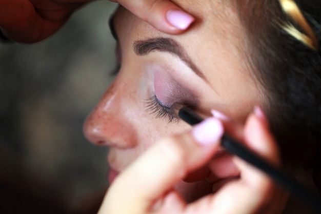 Artista de maquillaje de boda haciendo un maquillaje para la novia