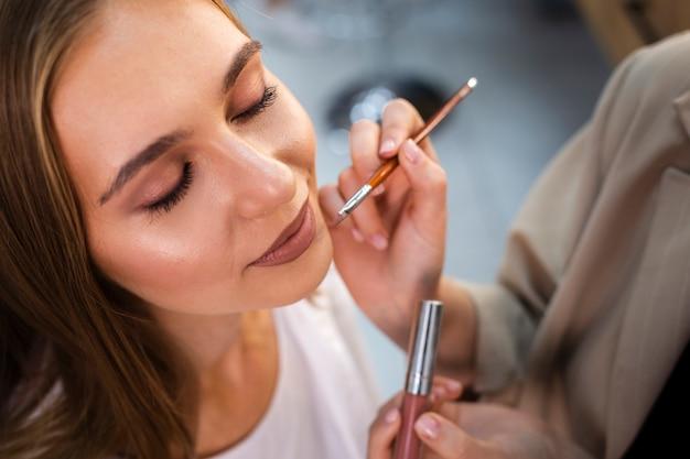 Artista de maquillaje de cerca aplicando lápiz labial desnudo en mujer con pincel