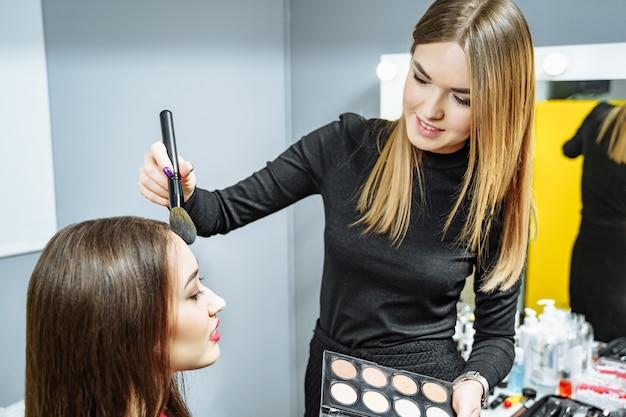 Artista de maquillaje creando maquillaje hermoso para la modelo morena.