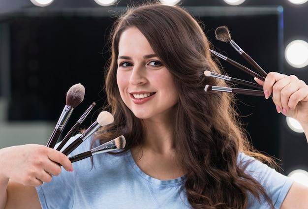 Artista de maquillaje feliz de la mujer con los cepillos