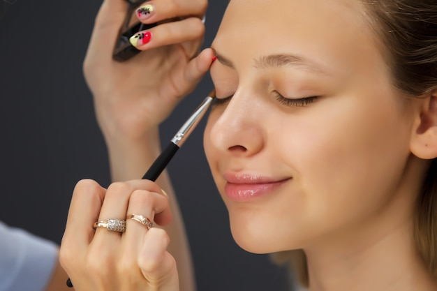 Artista de maquillaje femenino compone linda mujer joven hermosa en salón de belleza. atención al cliente en salón interior para crear una imagen sorprendente. asistente de creación de maquillaje de trabajo. concepto de satisfacción de belleza