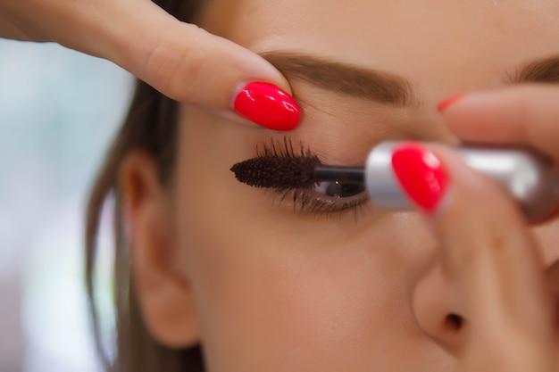 Artista de maquillaje femenino compone linda mujer joven hermosa en salón de belleza.