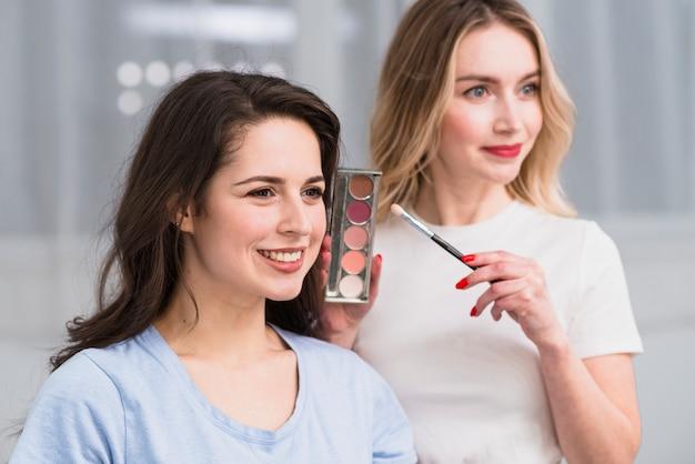 Artista de maquillaje femenino que muestra la paleta de sombra de ojos con estilo