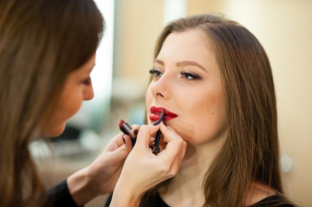Artista de maquillaje hace cambio de imagen hermosa chica