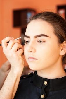 Artista de maquillaje haciendo maquillaje de una hermosa joven en el estudio