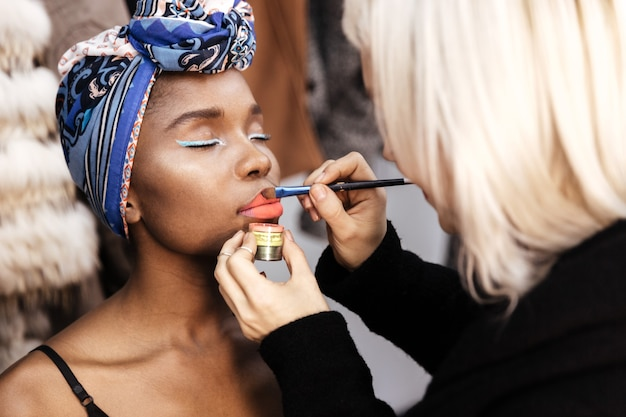 Artista de maquillaje haciendo maquillaje para joven hermosa modelo