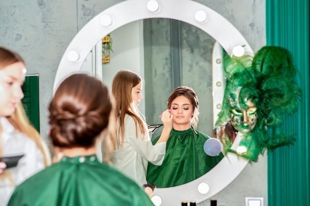 Artista de maquillaje haciendo maquillaje profesional para mujer joven en salón de belleza.