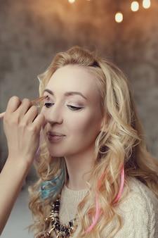 Artista de maquillaje con hermosa mujer rubia