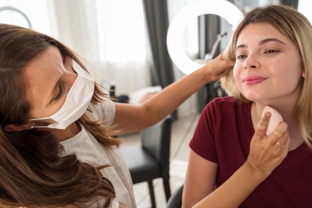 Artista de maquillaje con máscara aplicando base facial